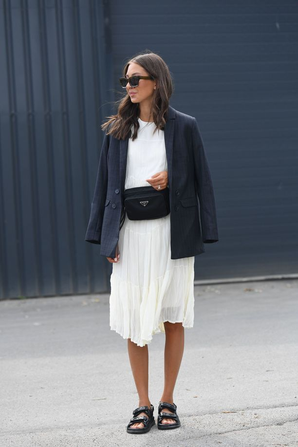 Девушка в белом легкм платье, черном блейзере и спортивных сандалиях