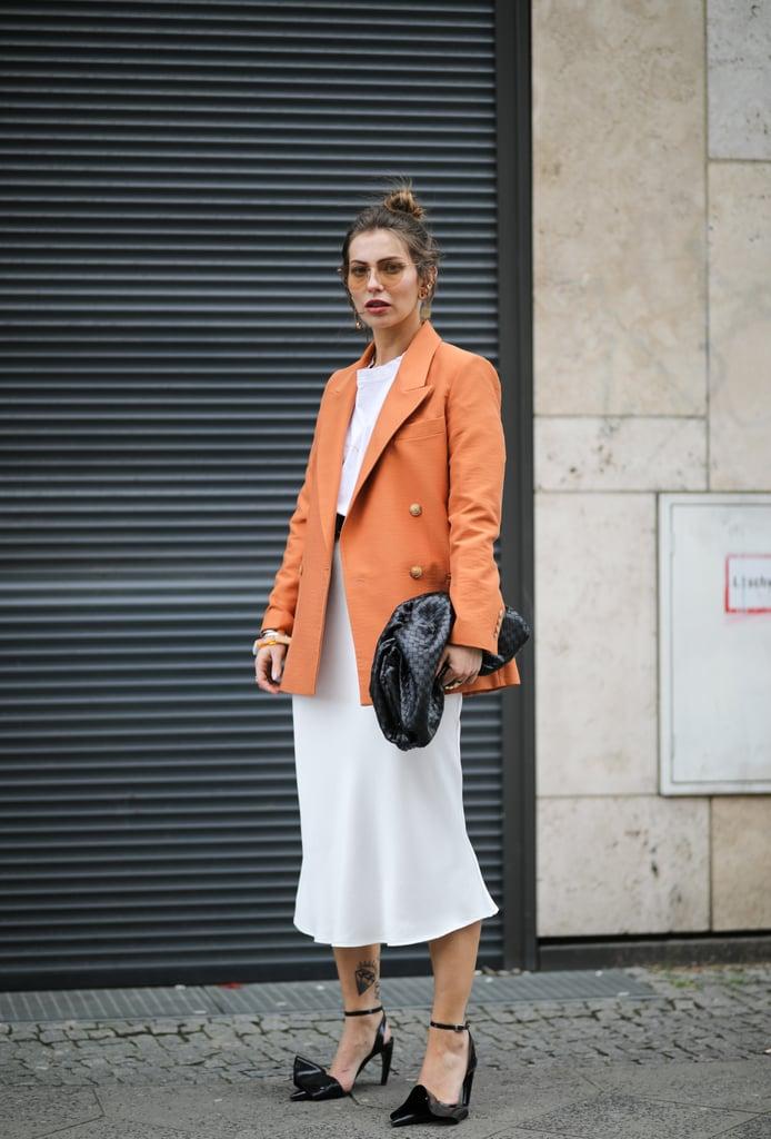 Девушка в белом платье, оранжевый блейзер оверсайз и черные туфли