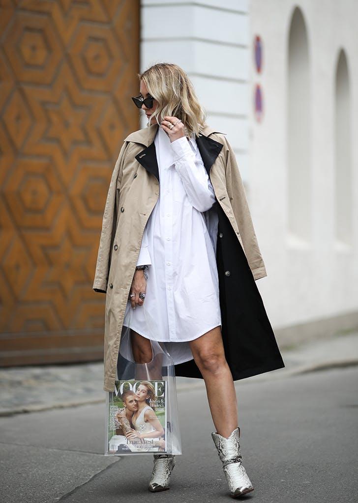 Девушка в белом платье рубашка, бежевый плащ и модные ботильоны