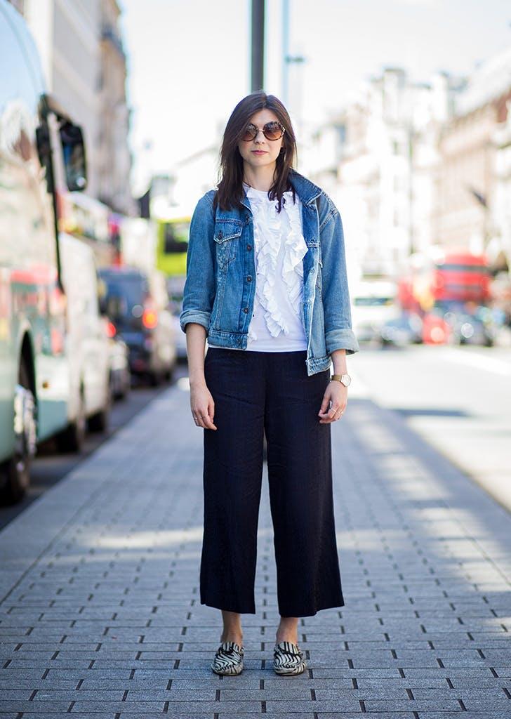 Девушка в белом топе, джинсовая куртка и черные широкие брюки