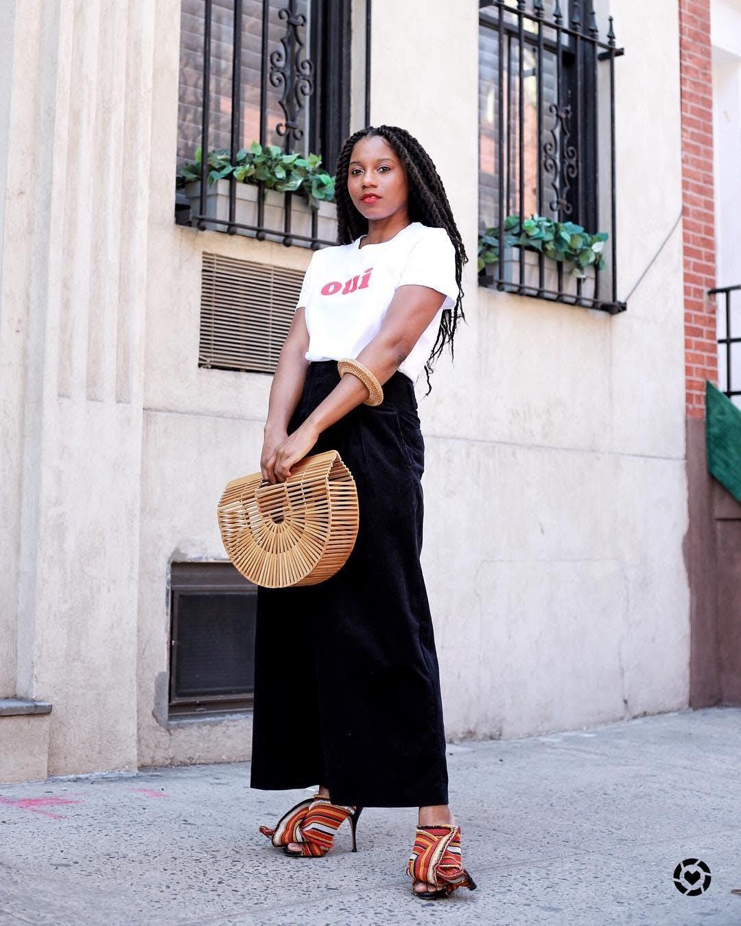 Девушка в белой футболке, черная юбка макси и соломенная сумка