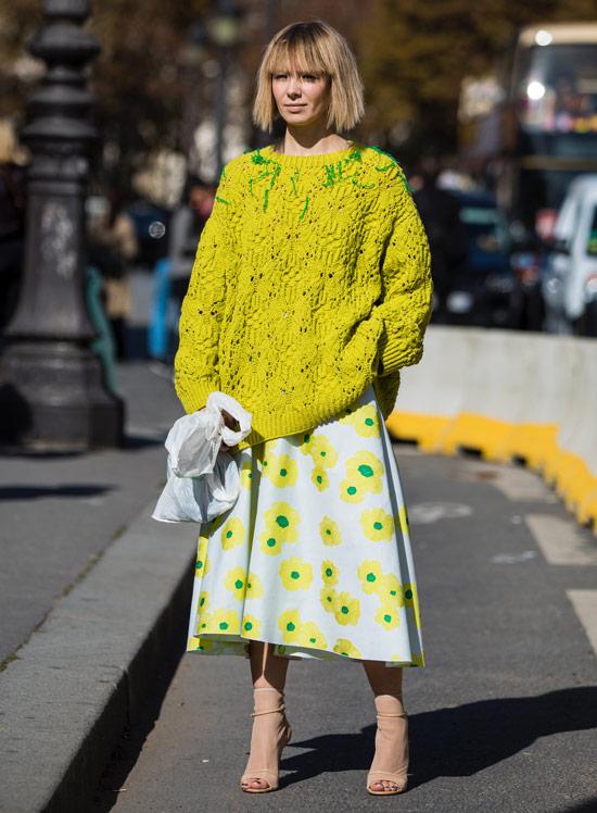 Девушка в белой юбке с цветами, желтый свитер оверсайз и бежевые босоножки