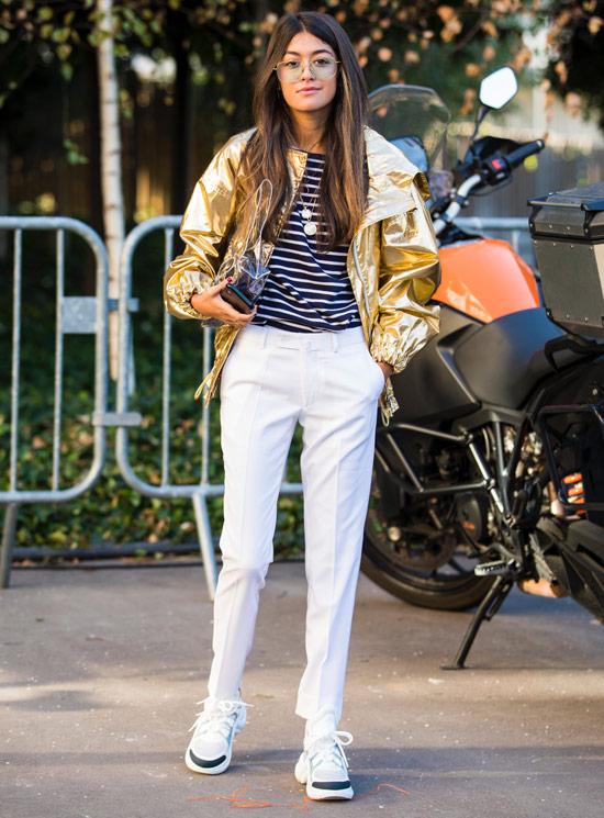Девушка в белых брюках, топ в полоску и золотой бомбер
