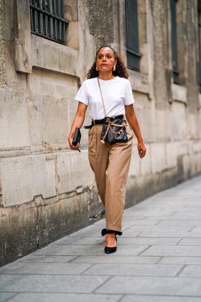 Девушка в бежевых брюках, простая футболка и черные аксессуары