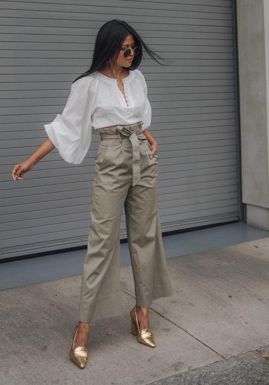 Девушка в бежевых широких брюках, белая блузка и золотые туфли