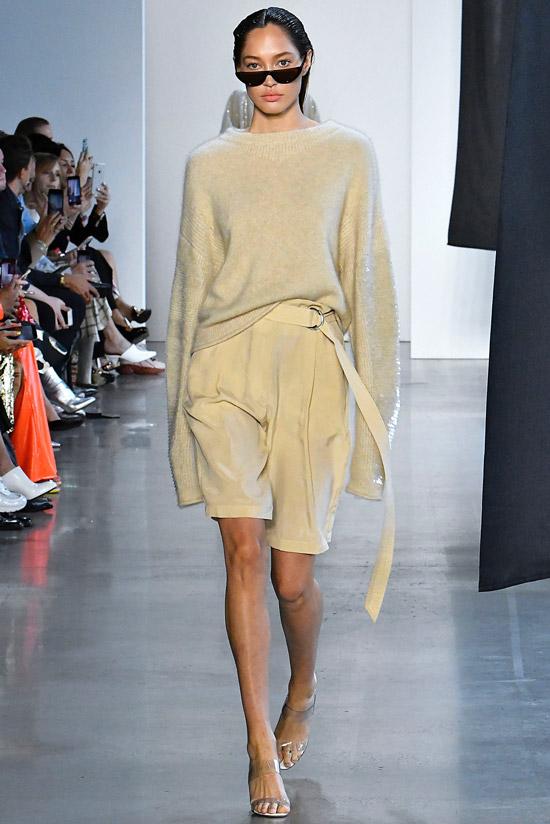 Девушка в бежевых шортах, джемпер и босоножки