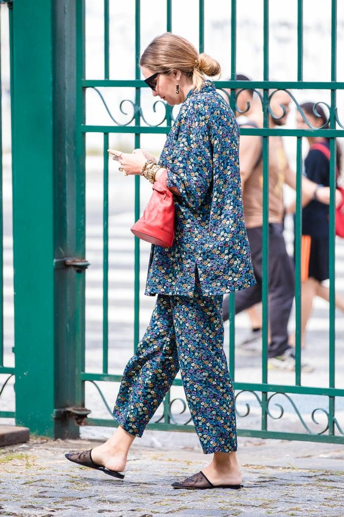 Девушка в брючном костюме с цветочным принтом и сандалии на плоской подошве