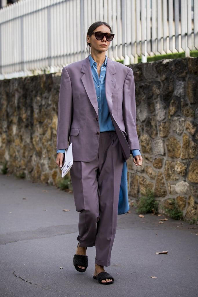Девушка в брючном костюме в деловом стиле и плоские сандалии