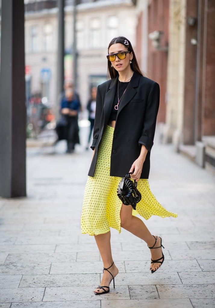Девушка в черном блейзере, кроп топ и желтая юбка миди