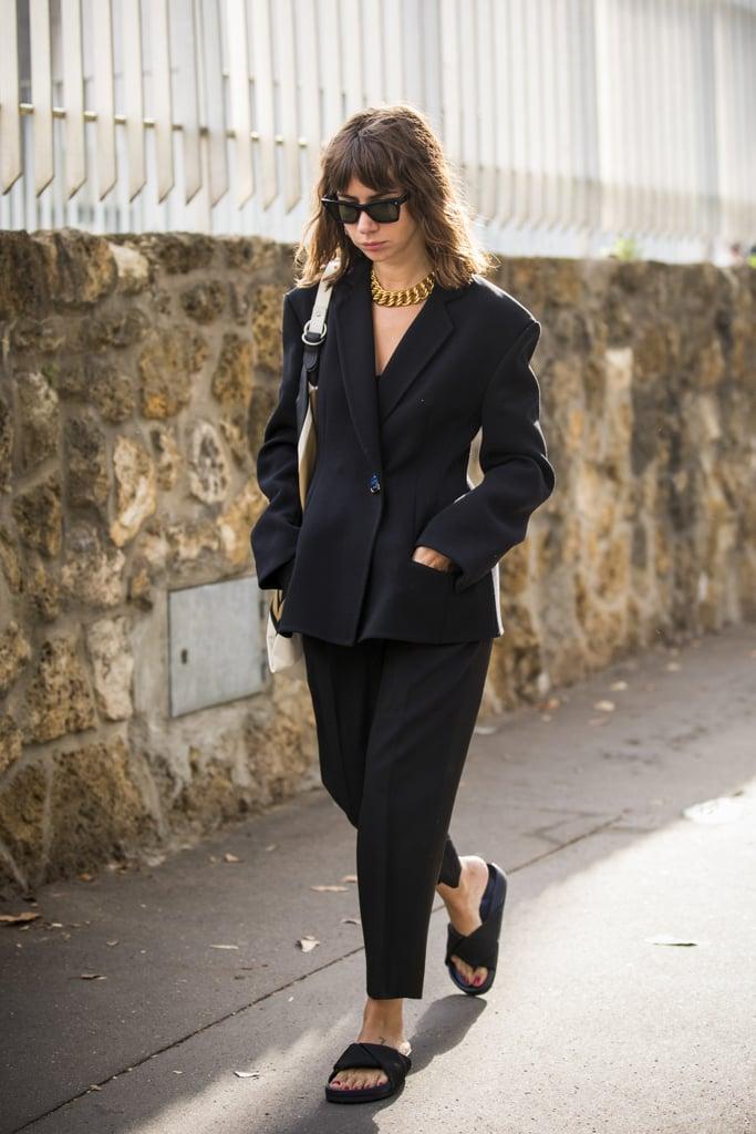 Девушка в черном брючном костюме и плоских сандалиях