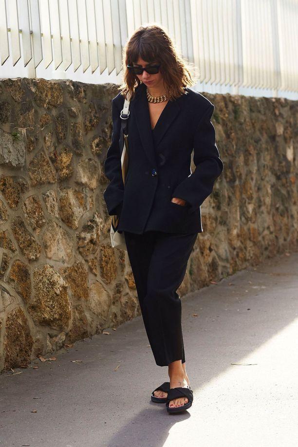 Девушка в черном брючном костюме и спортивных сандалиях