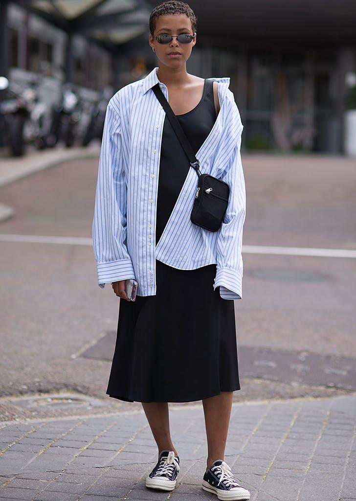 Девушка в черном простом платье, рубашка оверсайз в полоску и кеды