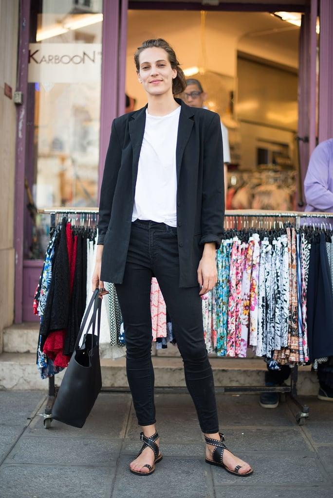 Девушка в черных джинсах, белая футболка, черный блейзер и сандалии