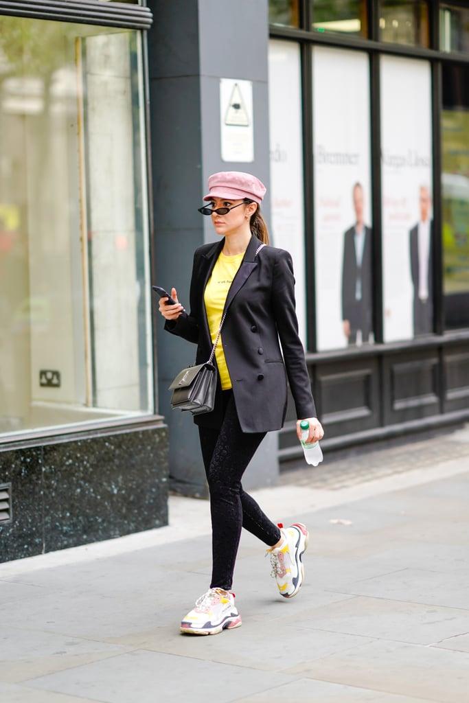 Девушка в черных леггинсах, елтая футболка и блейзер