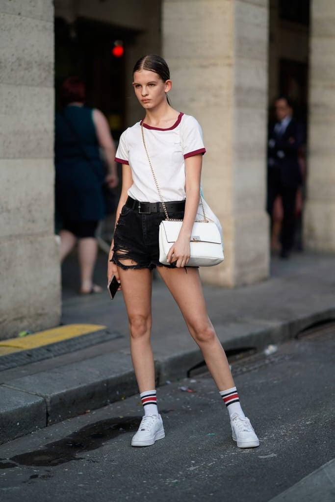 Девушка в черных шортах, белая футболка и кеды