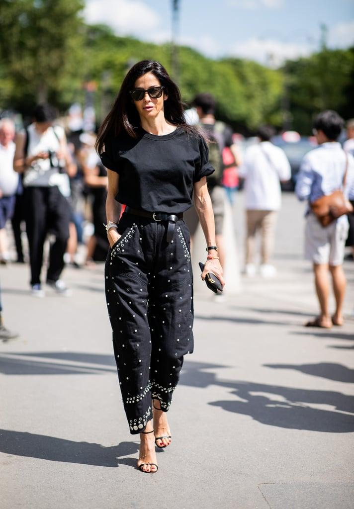 Девушка в черных штанах с ремнем, футболка и черные босоножки