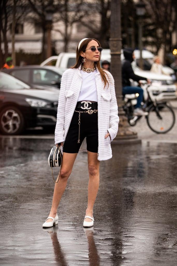 Девушка в черных велосипедных шортах, блейзер и белая футболка