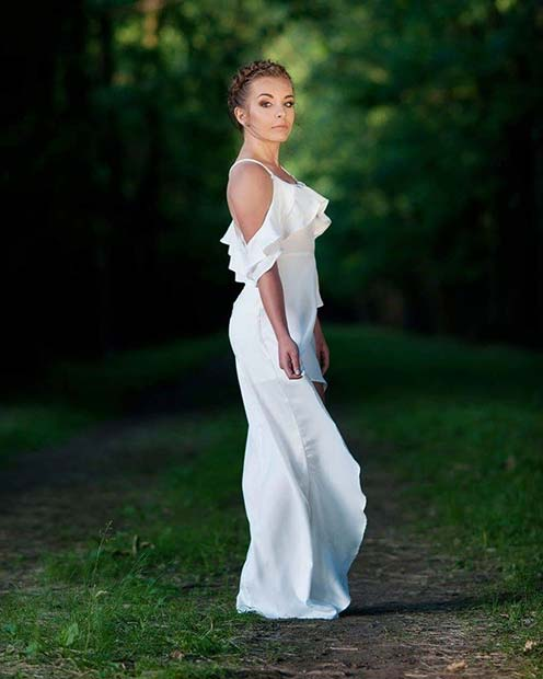 Девушка в длинном белом сарафане с рюшами и открытыми плечами