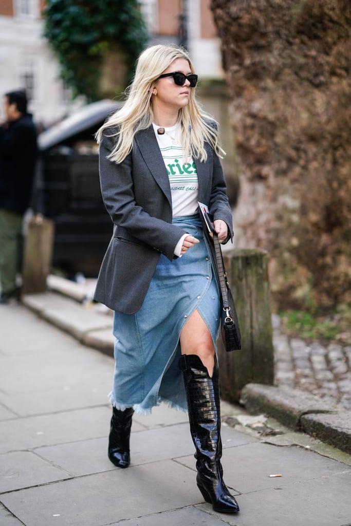 Девушка в джинсовой юбке, сапоги по колено, футболка и серый блейзер