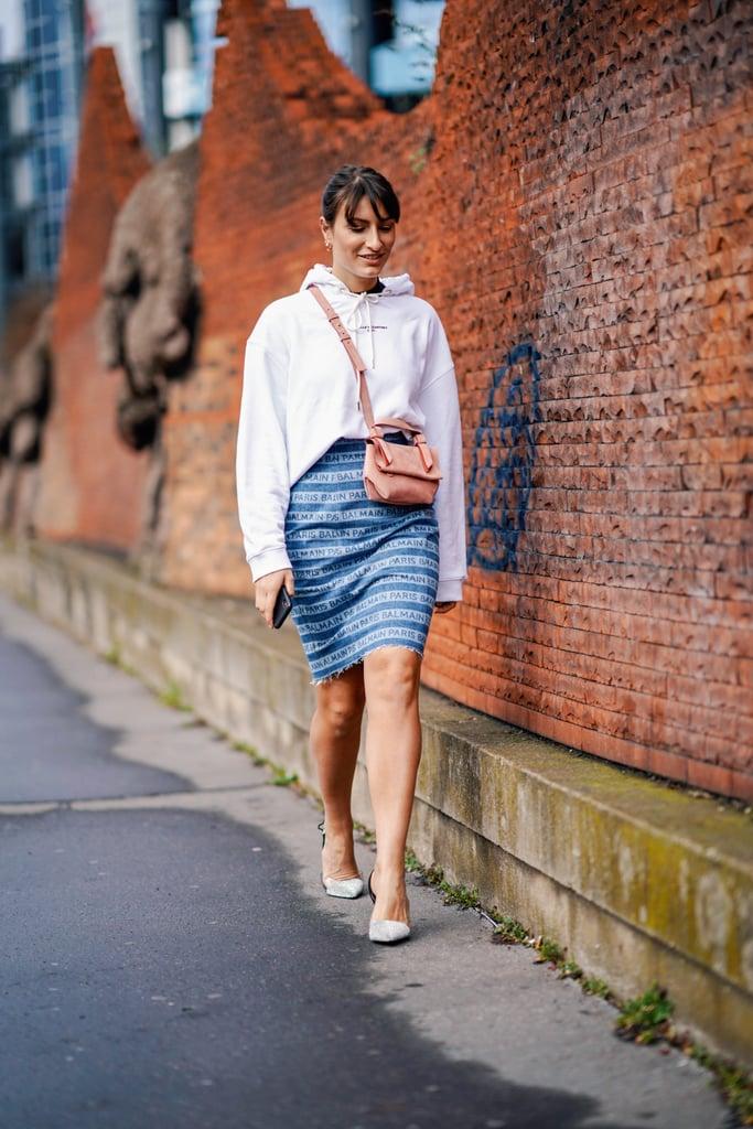 Девушка в джинсовой юбке, белое худи и туфли