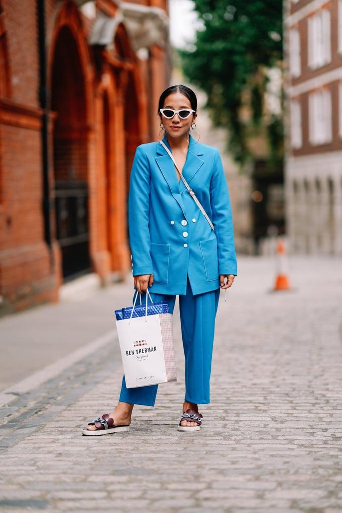 Девушка в голубом костюме с пиджаком оверсайз и сандалии