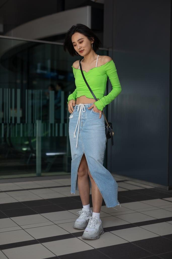 Девушка в голубой джинсовой юбке, зеленый кроп топ и кроссовки