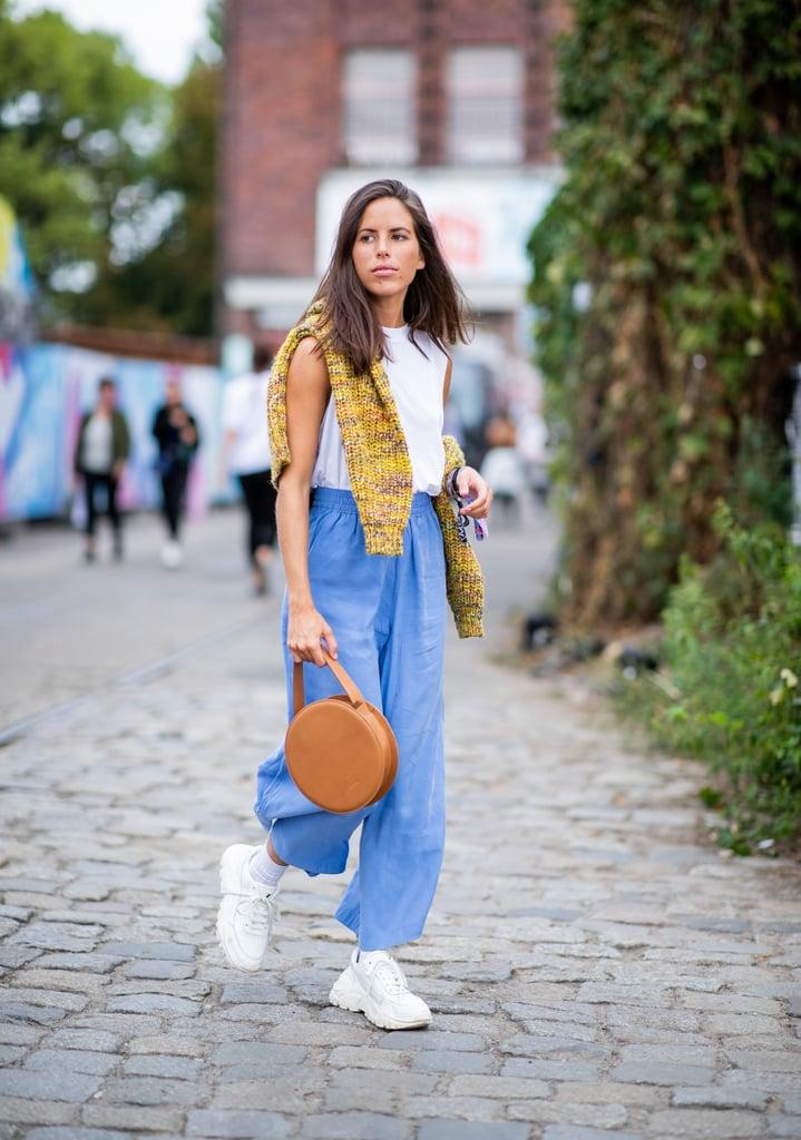 Девушка в голубых брюках, белая майка и кроссовки