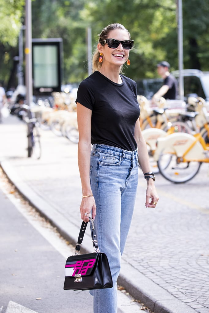 Девушка в голубых джинсах, черная футболка и сумка