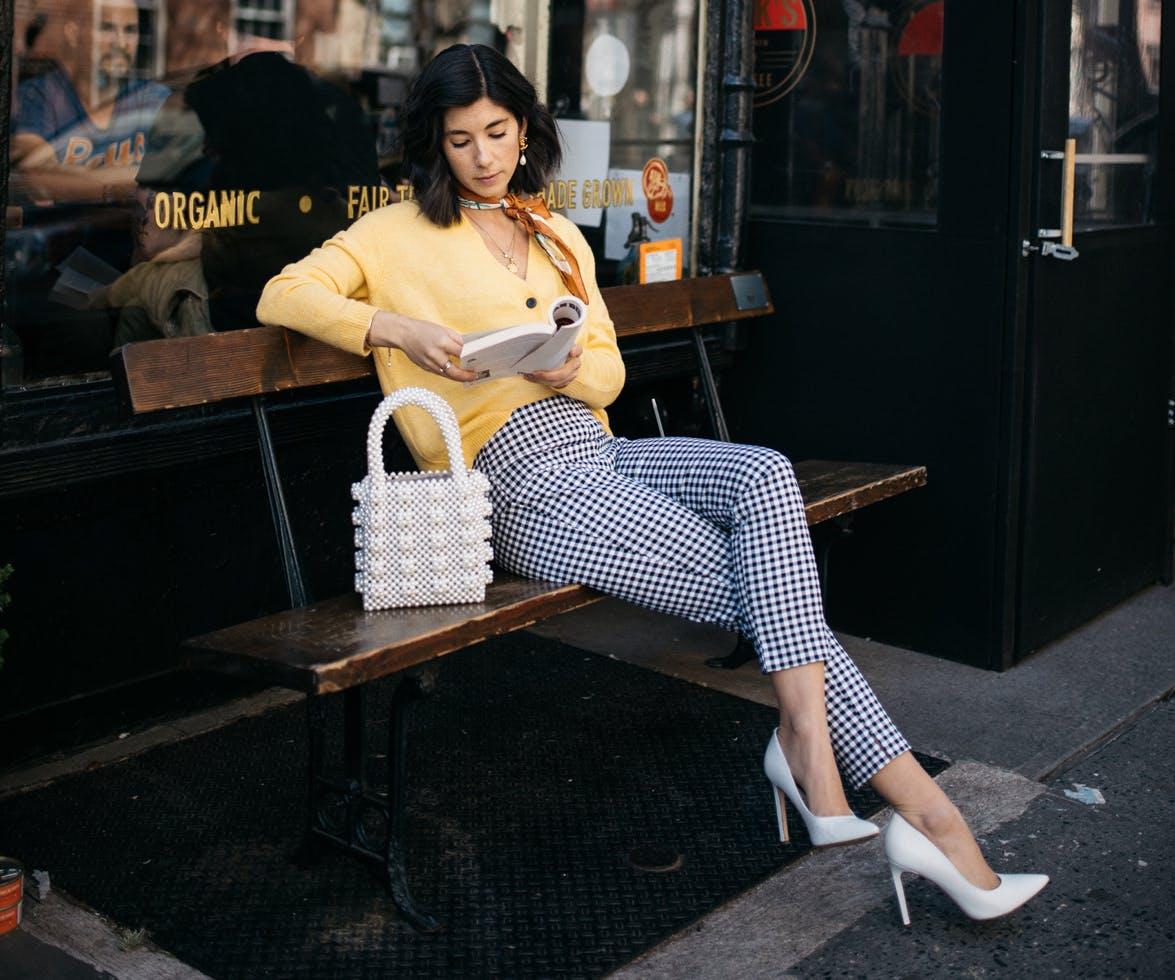 Девушка в капри в клетку и желтый джемпер, белые туфли на шпильке и сумка