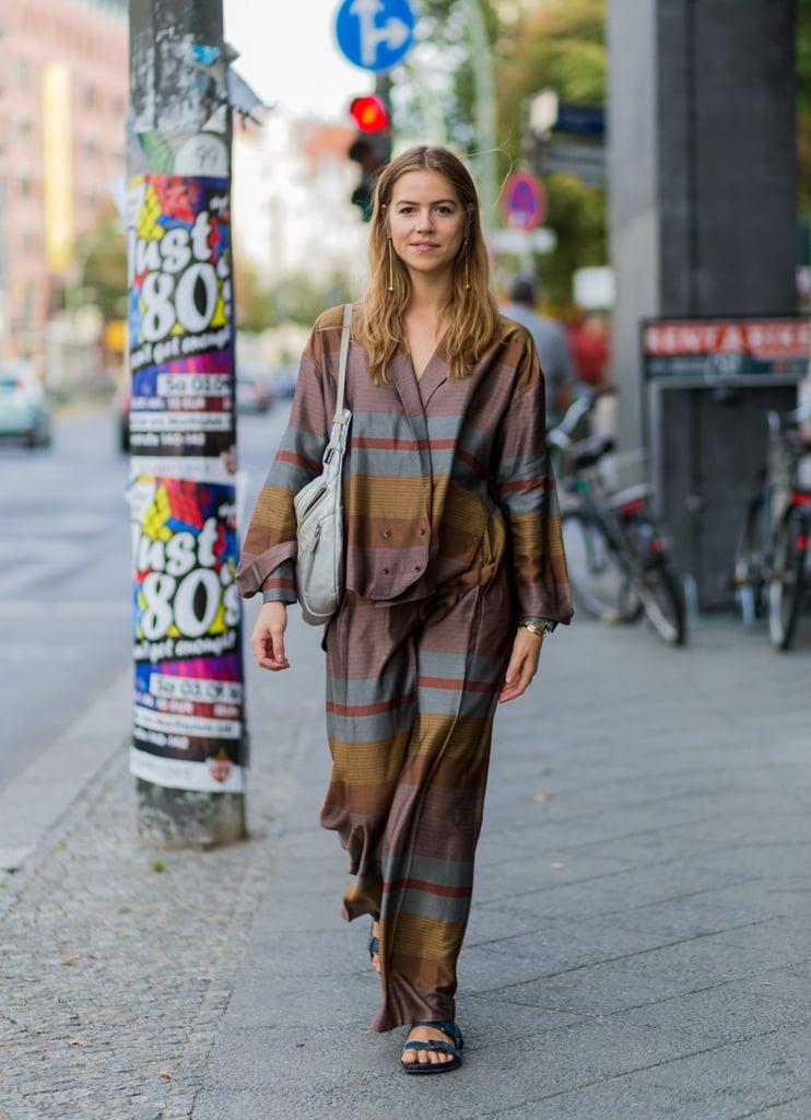 Девушка в коричневом брючном костюме в пижамном стиле и сандалиях