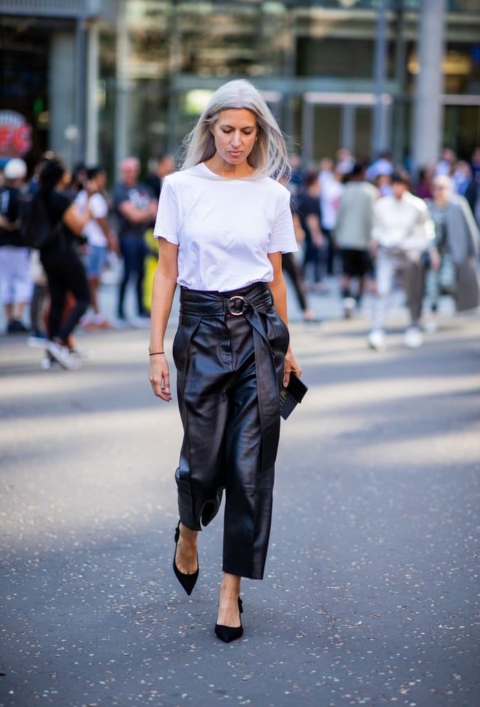 Девушка в кожанных брюках, белая футболка и черные туфли