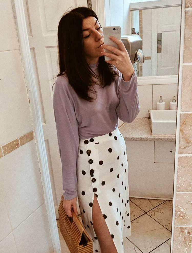 Девушка в лиловой водолазке и белой юбке в горох на пуговицах