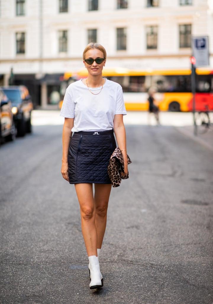 Девушка в мини юбке, белая футболка и белые ботильоны