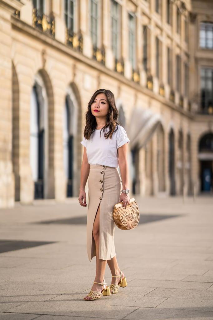 Девушка в облегающей юбке миди, белая футболка и деревянная сумка