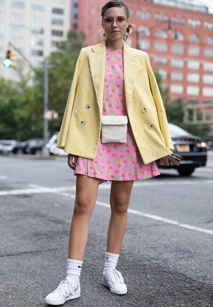 Девушка в розовом мини платье, елтый блейзер и белые кроссовки