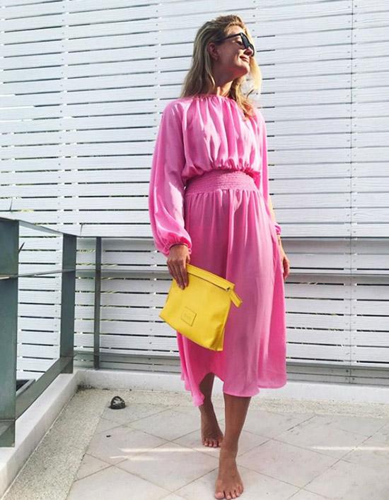 Девушка в розовом платье с длинными рукавами и елтый клатч