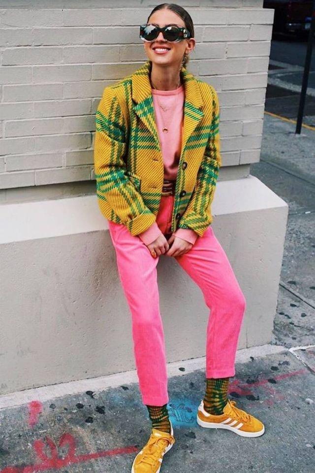 Девушка в розовых брюках, желтая куртка в клетку и кеды