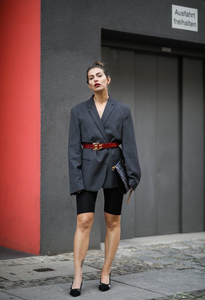 Девушка в сером блейзере оверсайз, велосипердные шорты и туфли