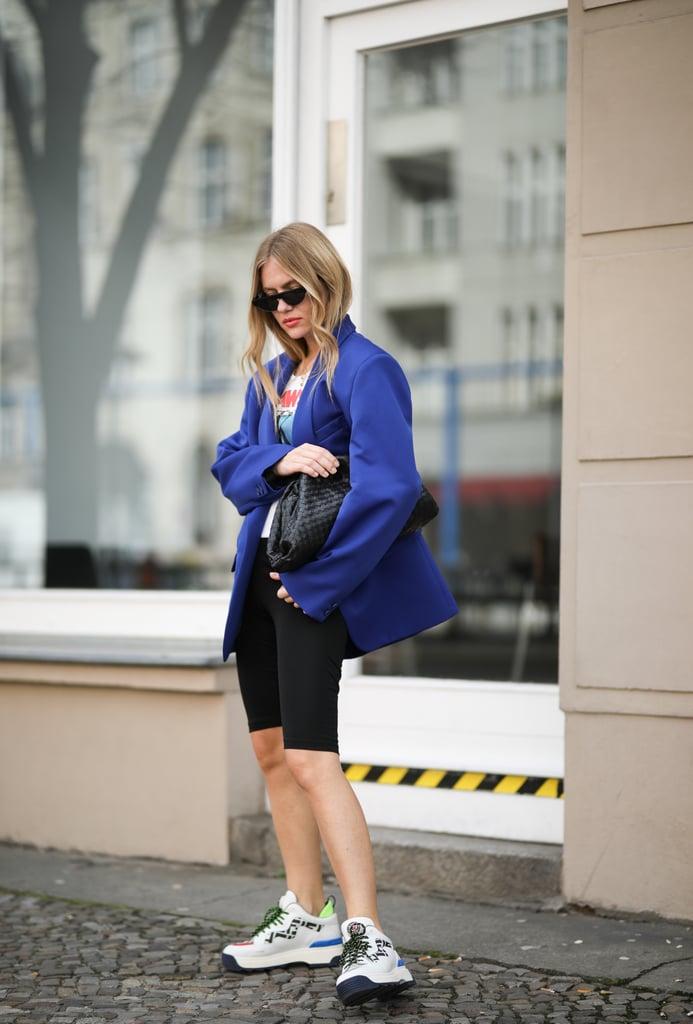 Девушка в синем блейзере оверсайз, влосипедные шорты и кроссовки