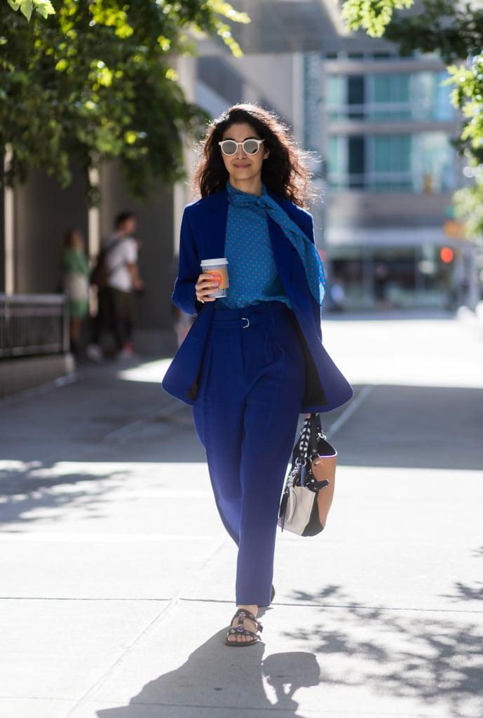 Девушка в синем брючном костюме, блузка и сандалии