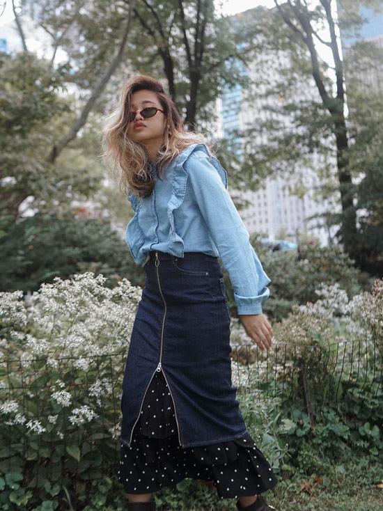 Девушка в темной джинсовой юбке и голубая блузка с рюшами
