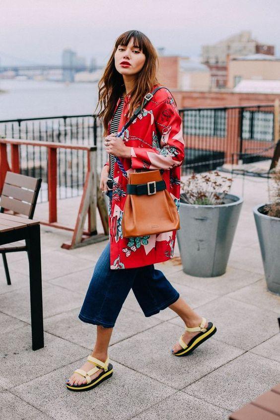 Девушка в укороченных джинсах, красный плащ и спортивные сандалии