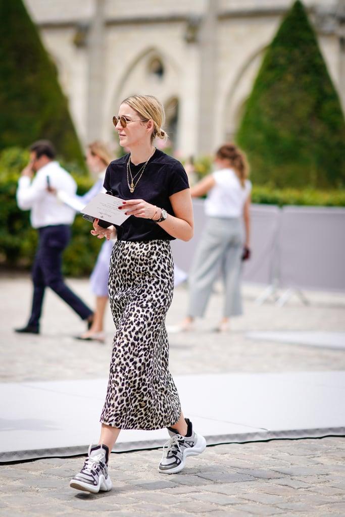 Девушка в узкой юбке, черная футболка и кроссовки
