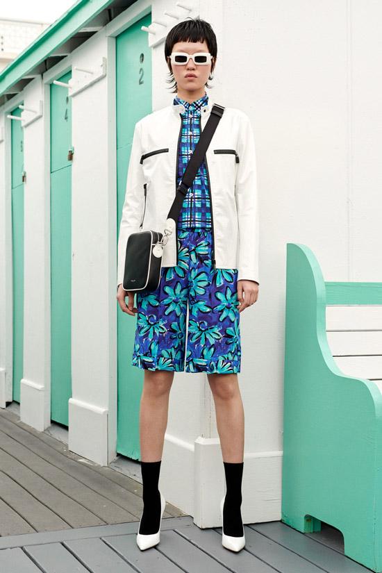 Девушка в ярких шортах с принтом, синяя рубашка в клетку, белый жакет и туфли
