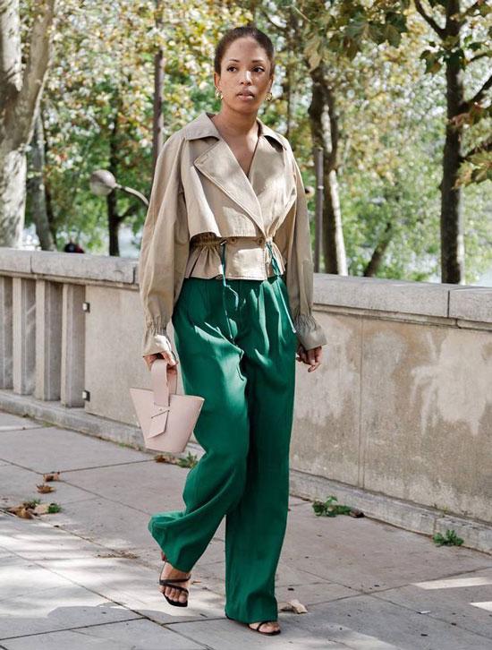 Девушка в зеленых широких брюках и бежевой куртке