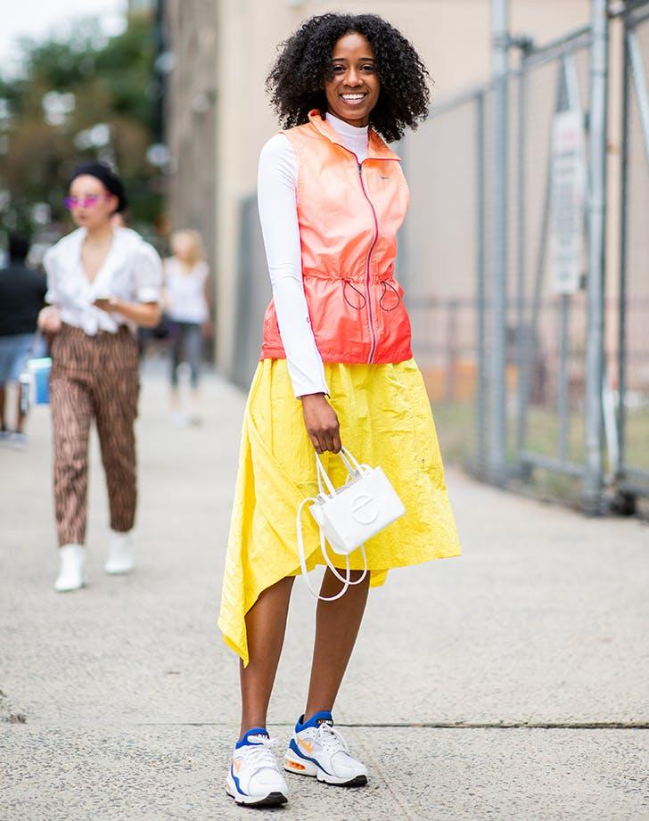 Девушка в желтой юбке мижи, оранжевая жилетка и кроссовки