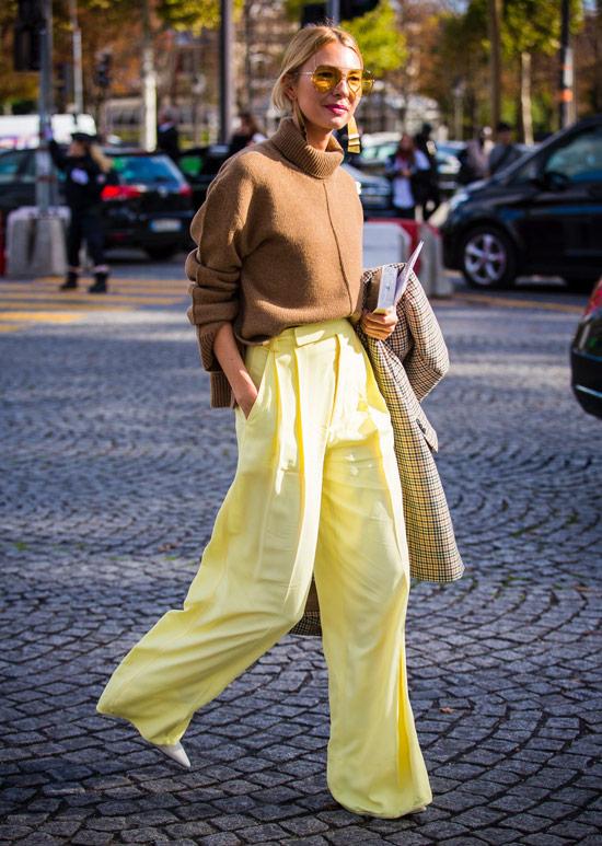 Девушка в желтых широких брюках, коричневый свитер
