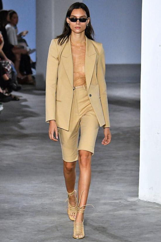 Модель в бежевом костюме с шортами бермудами и босоножки