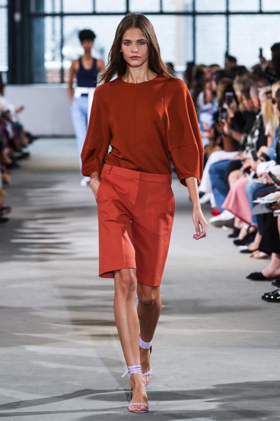 Модель в оранжевых шортах бермудах, свитшот и красивые босоножки