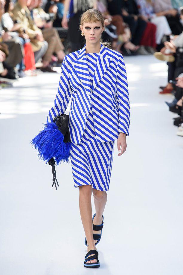 Модель в платье и жакете с бело-синюю полоску, черные сандалии
